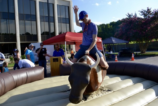 AtlanticBT employee on mechanical bull with hand in air