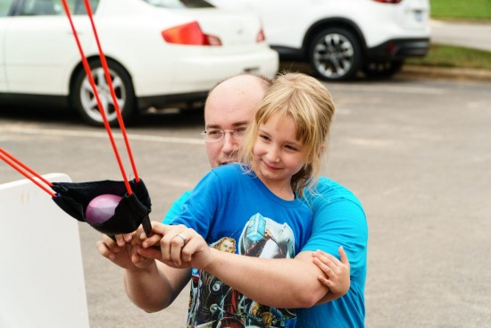 employee helping daughter with water ballon slingshot