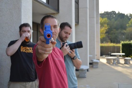 employee pointing paint ball gun at camera