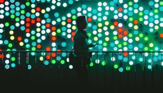 Man walking in front of lights