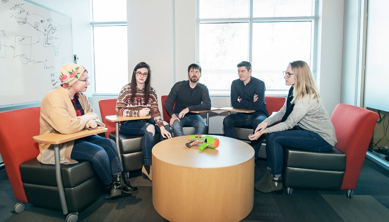 5 ABT employees around meeting table with nerf gun