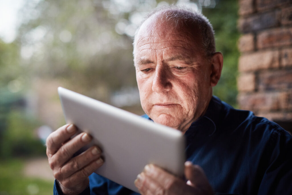 A senior man holds a digital tablet, looking down at it and frowning in confusion or worry.